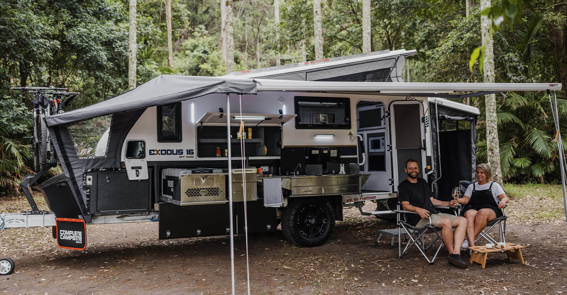 Couple drinking a wine in their camper trailer.